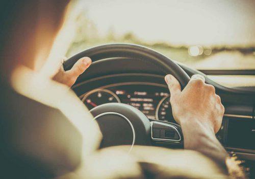 Conducteur au volant de sa voiture d'occasion
