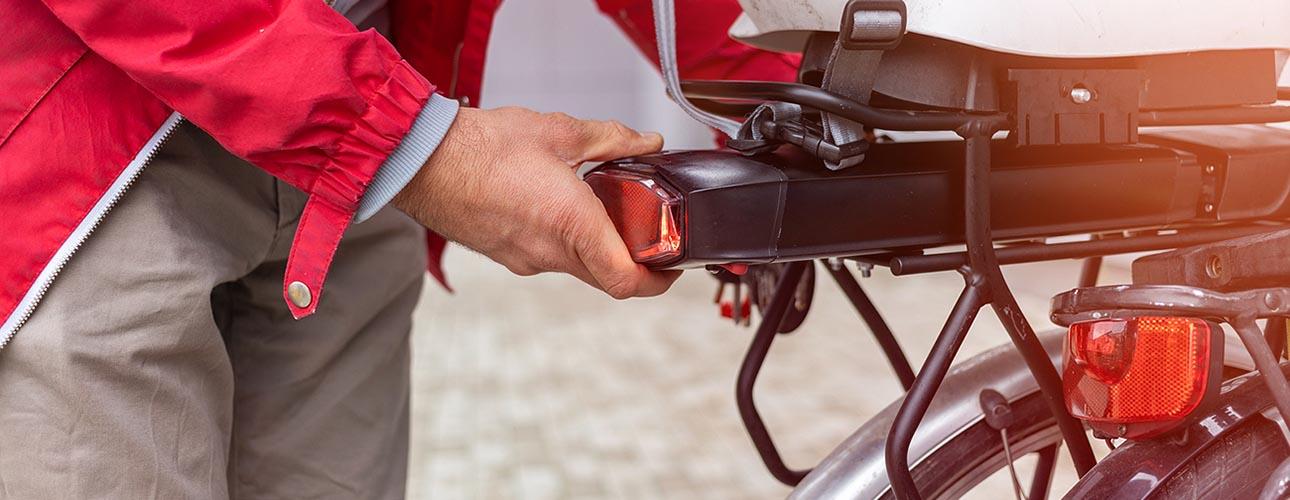 Een gebruiker van een elektrische fiets haalt de batterij uit zijn fiets
