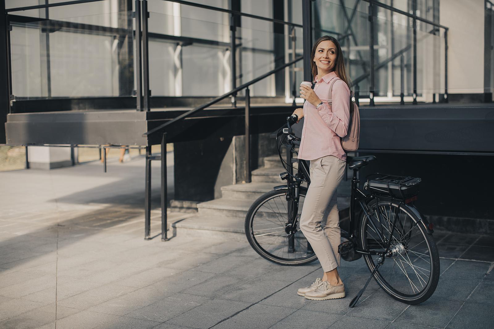 Jonge vrouw naast elektrische fiets