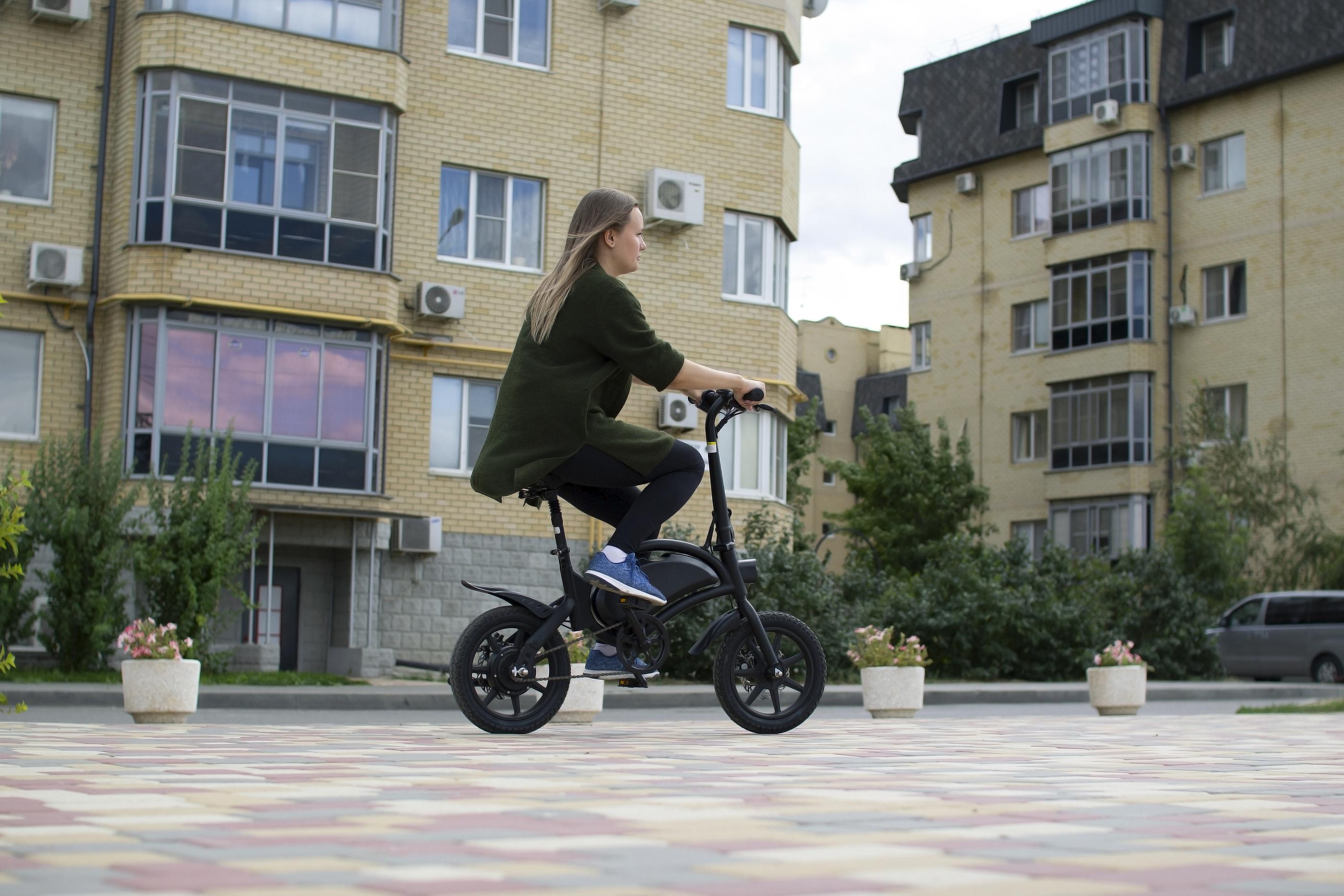 Jeune femme roulant avec un vélo électrique pliable