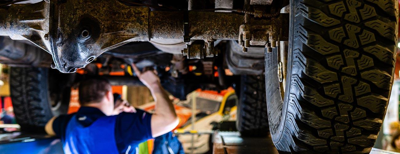 Mécanicien effectuant un contrôle technique sous le véhicule