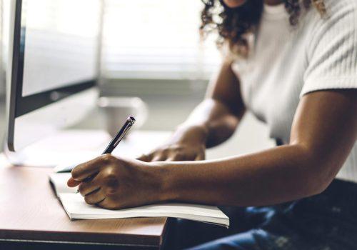 Une jeune femme écrivant dans un carnet