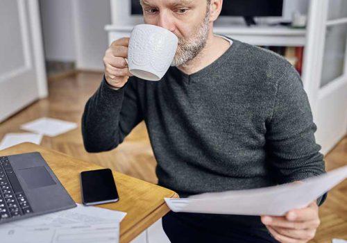 Employé en télétravail, buvant un café et lisant un dossier