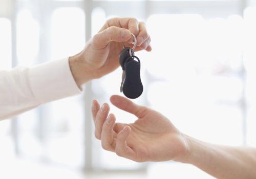 Main tendant une clé lors de l'achat d'une voiture d'occasion